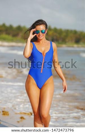 Pretty young woman in blue swimsuit walking on seashore #1472473796