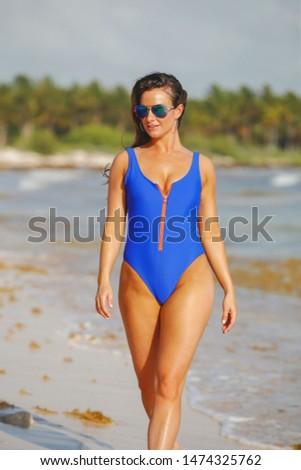 Pretty young woman in blue swimsuit walking on seashore #1474325762