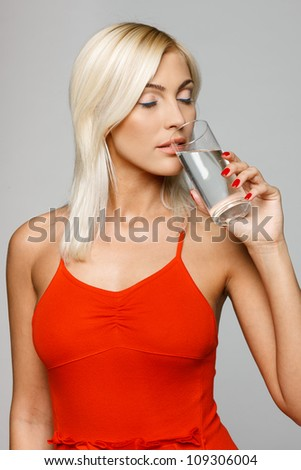 Pretty young woman in bright red dress enjoying fresh water with closed eyes, over gray background