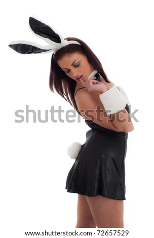 Pretty young woman in bunny outfit isolated against white