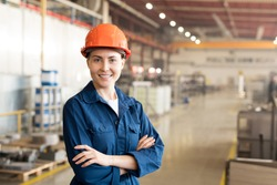 Pretty young woman in helmet and workwear looking at you while standing in workshop or factory