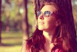 Pretty young woman in sunglasses on the natural background