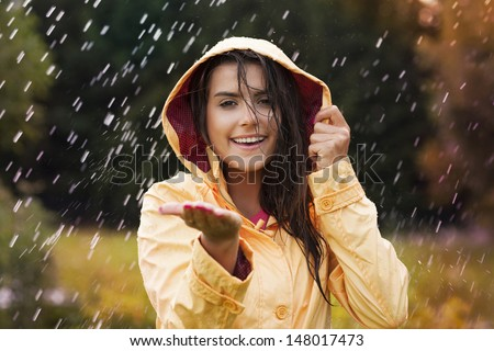 Pretty young woman in yellow raincoat