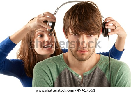 Pretty young woman interrupts man with headphones