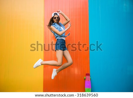 Pretty young woman is jumping with against the colorful wall.