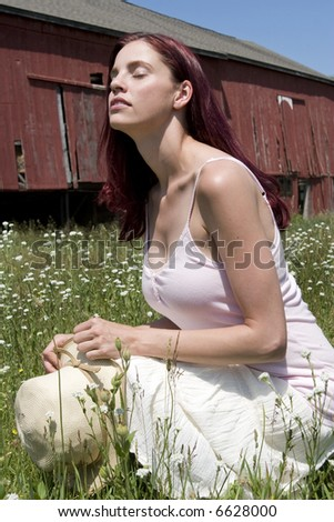 Pretty young woman kneeling with her eyes closed in a field of wild flowers with a red barn in the background.
