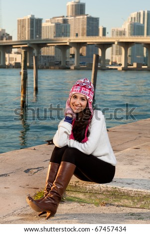 Pretty young woman lifestyle with winter clothing along a seawall on the bay with a downtown skyline at sunset.