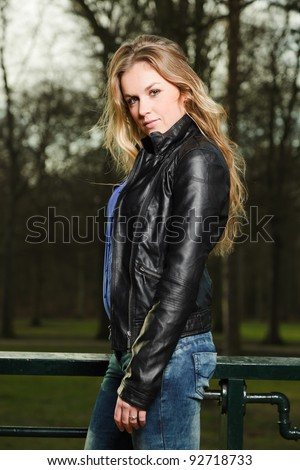 Pretty young woman long blond hair in winter forest wearing black