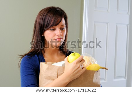 Pretty Young Woman Looking At A Fresh Yellow Apple