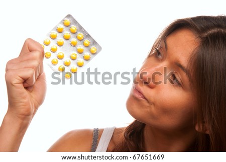 Pretty young woman looking at full medicine pack of yellow tablet pills thinking about doctor's prescription to take one or not isolated on a white background