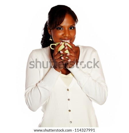 Pretty young woman looking at you while drinking a mug of coffee against white background