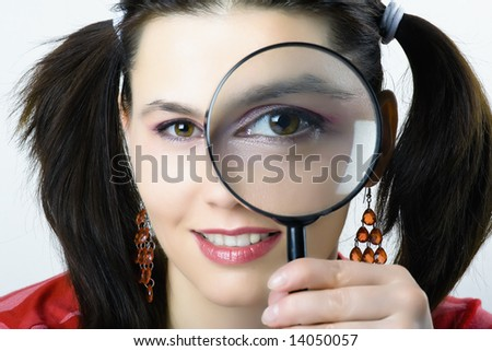 pretty young woman looking through magnifying