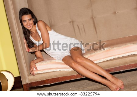 Pretty young woman lying on a art deco sofa in a trendy South Beach hotel lobby in Miami.