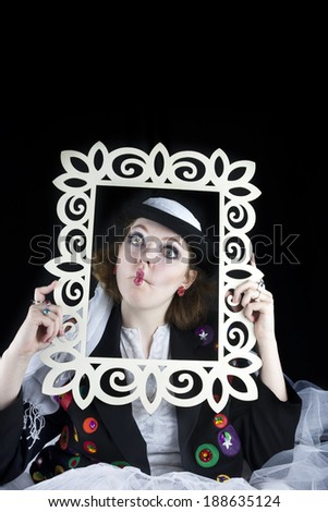Pretty young woman making funny face and holding picture frame wearing hat and crinoline