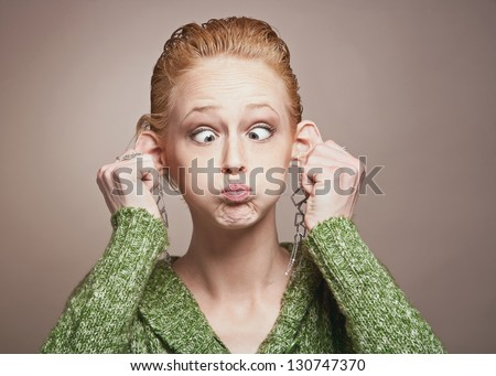 Pretty young woman making funny silly face - stock photo