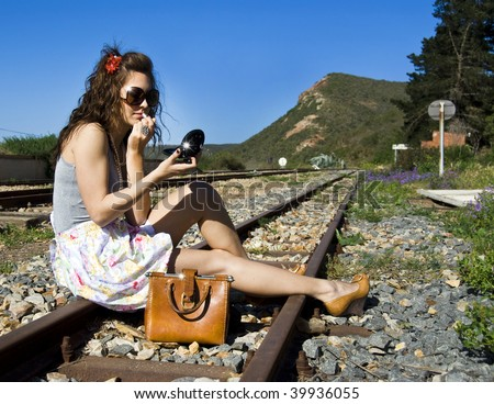 Pretty young woman missed her train and put on lipstick while she waits for the next train