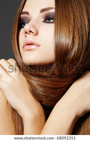 Pretty young woman model with shiny smooth hairstyle and brown smoky make-up. Health, beauty, wellness, hair and make-up. Beautiful fashion hairstyle