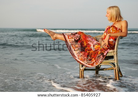 Pretty young woman on the chair/Pretty young woman sitting on the chair sourrounded by the sea