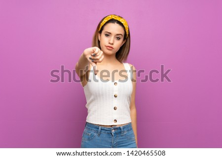 Pretty young woman over isolated purple wall showing thumb down with negative expression #1420465508