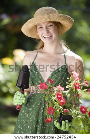 Pretty young woman planting flowers in her garden