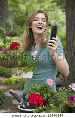 Pretty young woman planting flowers in her garden while on cell phone