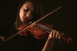 Pretty young woman playing a violin over black background