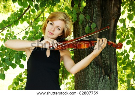 Pretty young woman playing the violin outdoor