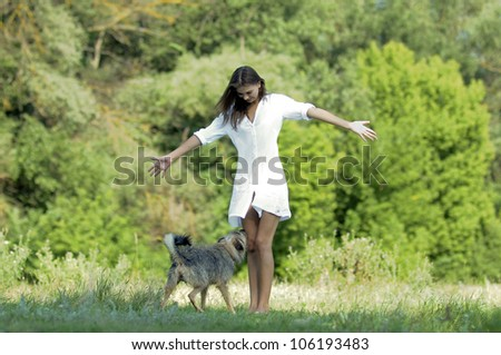 Pretty young woman playing with dog