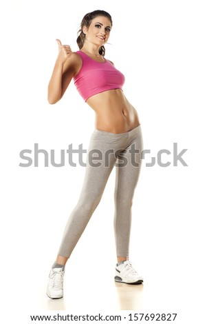 pretty young woman posing and showing thumb up during exercise on white background