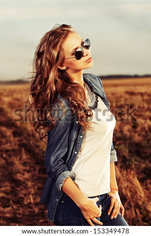 Pretty young woman posing outdoor at sunset