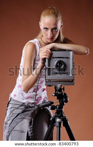 Pretty young woman posing with large format camera