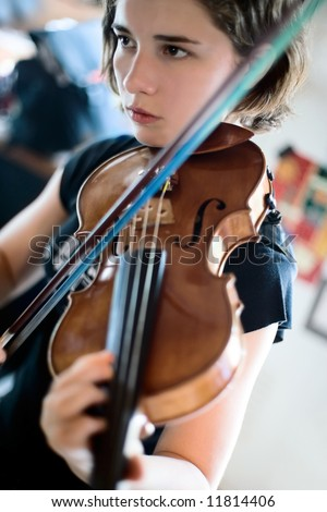 Pretty young woman practicing her violin with total concentration; soft focus