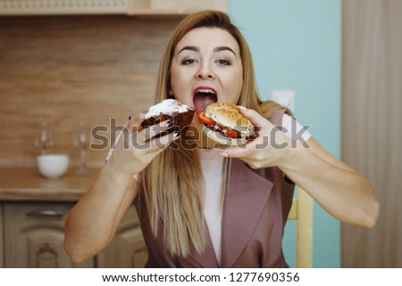 Pretty young woman prepared to eat a huge hamburger or cupcake. She opened her mouth in anticipation of gastronomic pleasure. The concept of healthy eating, the fight against excess weight. #1277690356