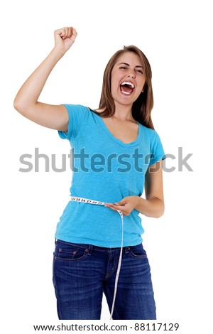 pretty young woman rejoicing over weight loss success. One hand holds a tape measure, the other is raised in triumph as she shouts for joy at her accomplishment