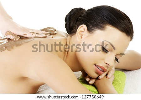 Pretty young woman relaxing being massaged in spa saloon with chocolate. Isolated on white