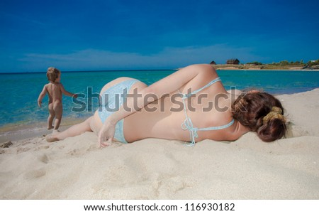 Pretty young woman relaxing on sea beach near her little baby