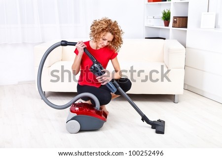 Pretty young woman repairing vacuum cleaner at home