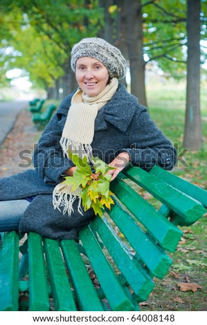 Pretty young woman resting on a bench in autumn park - stock photo