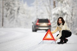 Pretty, young woman setting up a warning triangle and calling for assistance after her car broke down in the middle of nowhere on a freezing winter day