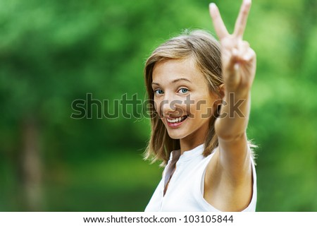 Pretty young woman showing gesture that everything is Victory, against green of summer park.