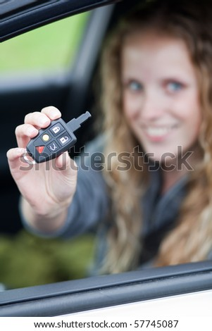 Pretty young woman showing off her brand new car - showing you the car keys