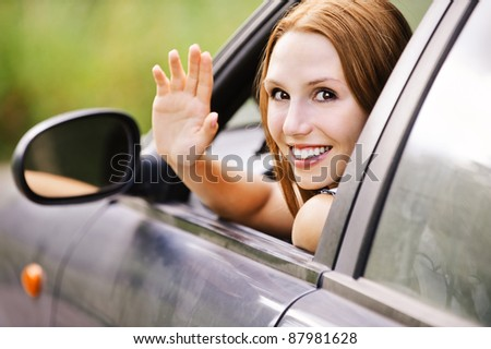 pretty young woman sitting car looking out window waving smiling