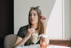 pretty young woman sitting in a cafe with a cup of coffee latte. Brunette girl in cafe with latte.