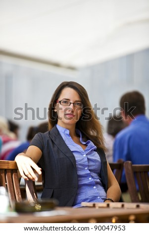 Pretty young woman sitting in a garden restaurants and enjoys her break from work.