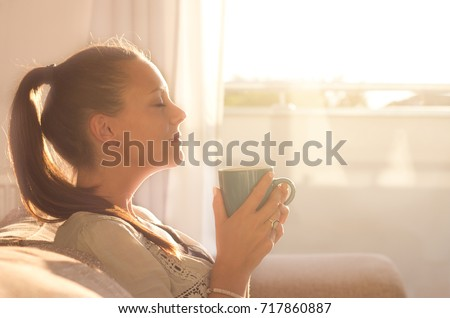 Pretty young woman sitting on sofa and enjoying first morning coffee on sunshine #717860887