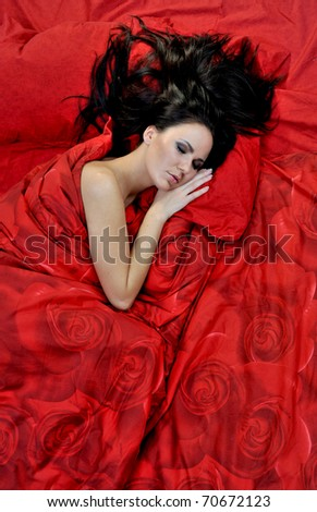 Pretty young woman sleeps on red linen