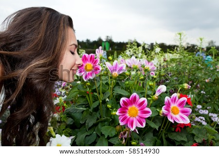Pretty young woman smelling the flowers from the Palace of Versailles Gardens