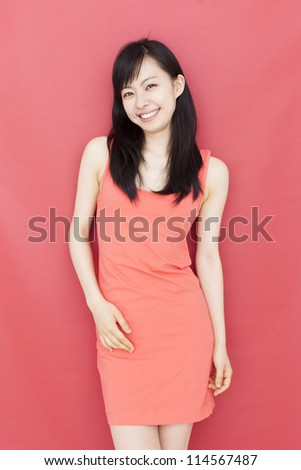 pretty young woman smiling against red background