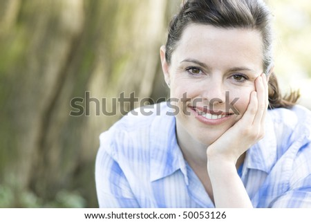 Pretty Young Woman Smiling To Camera With Cheek Resting on Hand
