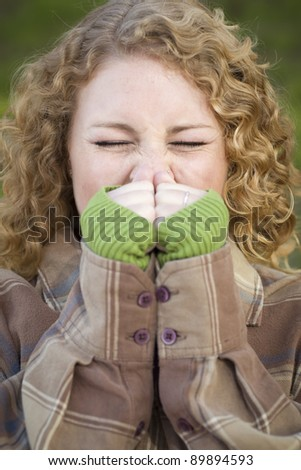 Pretty Young Woman Sneezing Outdoors.